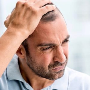 concerned mature man looking down with his hand in his balding head