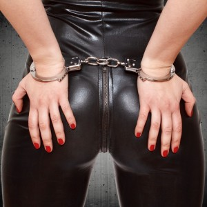 Sexy dominatrix hands on ass in handcuffs